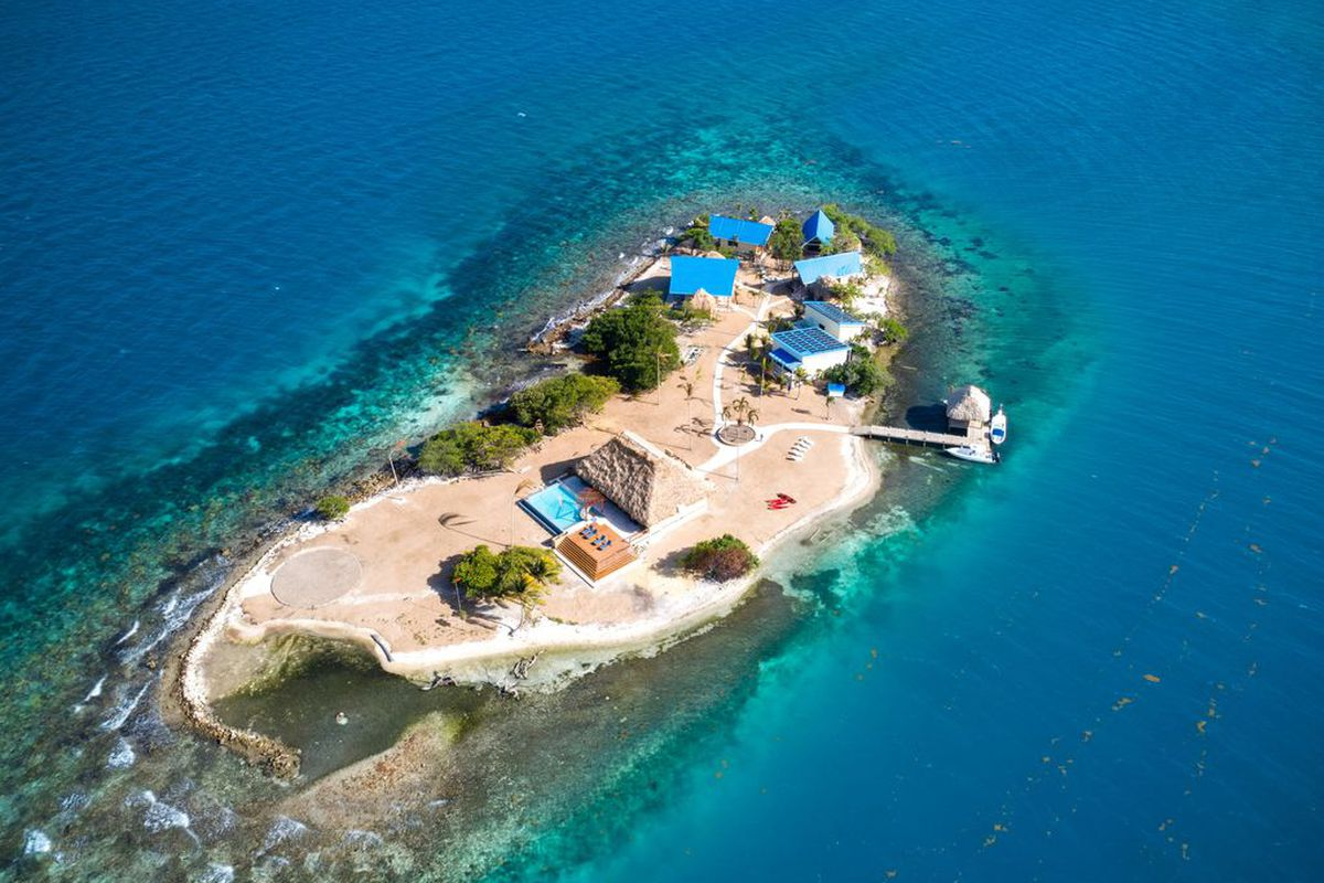 Aerial view of a private island in Belize surrounded by turquoise waters. A few buildings sit on one side of the island, where there's also a dock.