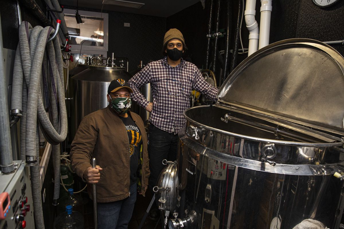 Two men wearing masks stand amid large pieces of brewing equipment.
