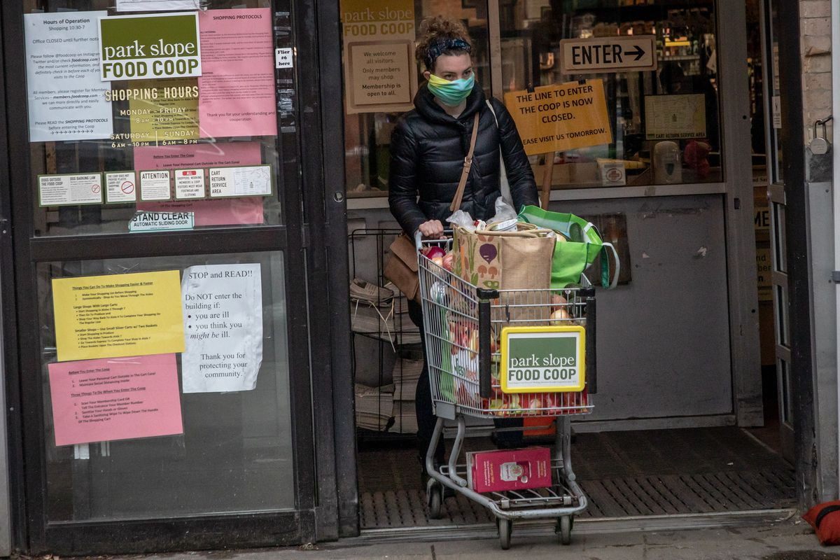 A woman wheels a cart full of groceries out of the Park Slope Food Coop