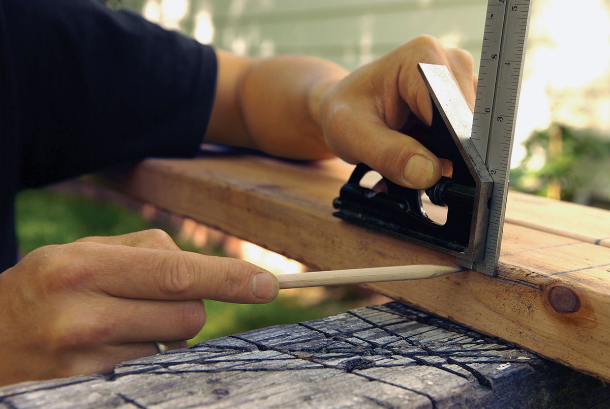 Man Uses Speed Square To Locate And Mark Notches Of Trellis Frame