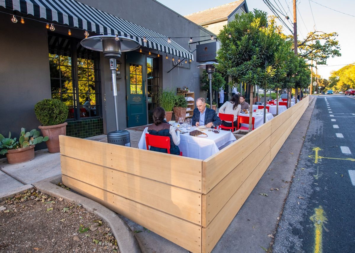 The outdoor street patio fenced in by a light wooden fence