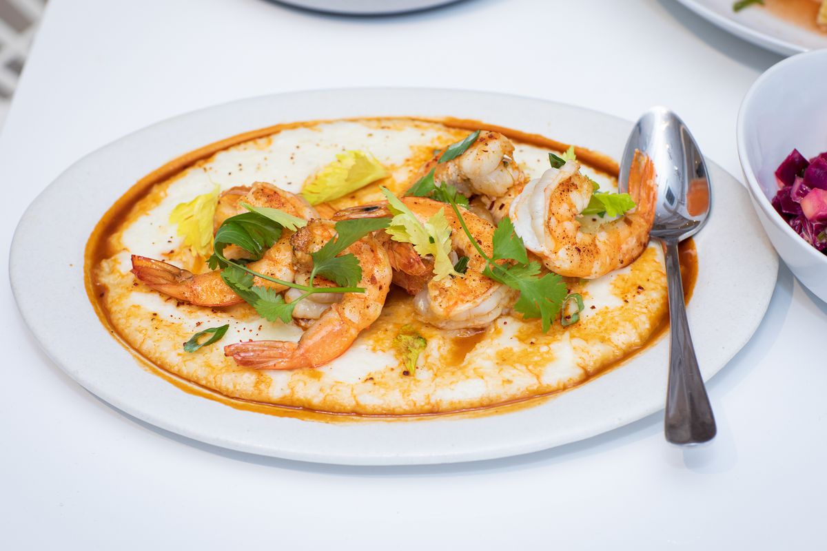 A plate of orange-white shrimp, yellow-ish grits, and a sprinkling of green herbs on top