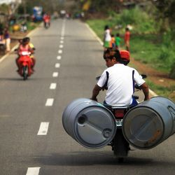 A man carries water barrels on a motorcycle in Tacloban, Friday, Nov. 22, 2013.