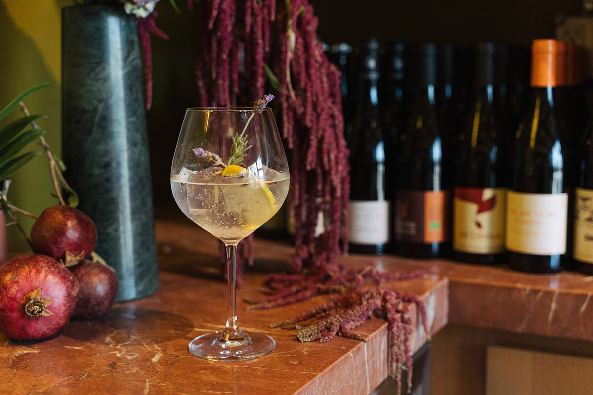 A wine glass filled with gin and tonic on the bar at Bodega Rosette.