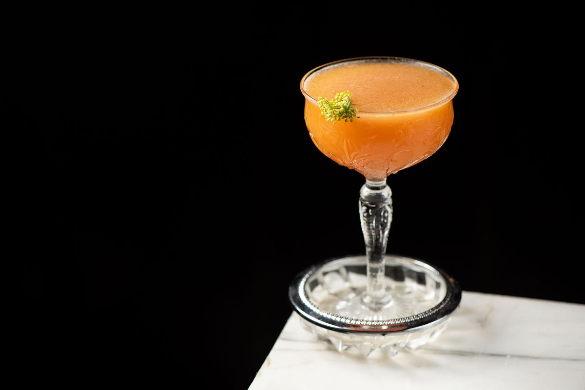 A cocktail in a pretty glass on the edge of a table.