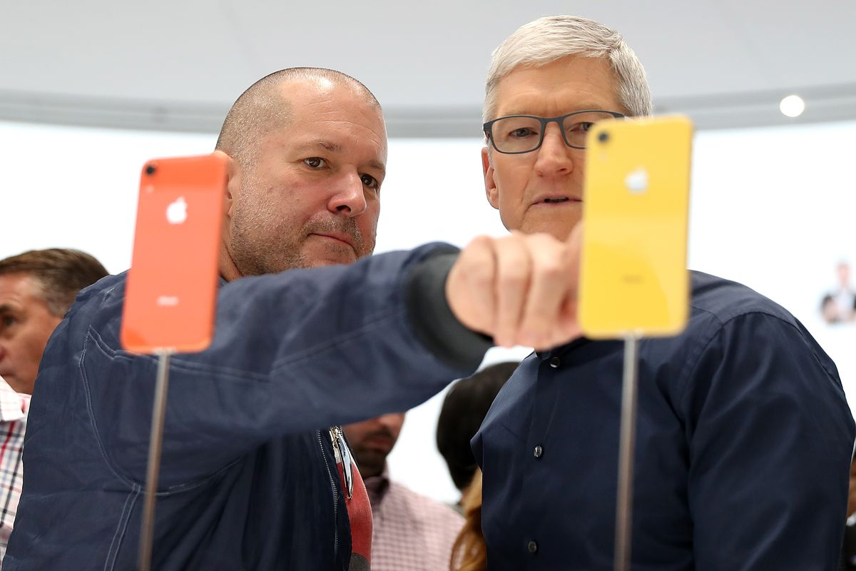 Apple Chief Design Officer Jony Ive points to an Apple iPhone while Apple CEO Tim Cook looks on at the 2018 Apple unveiling.