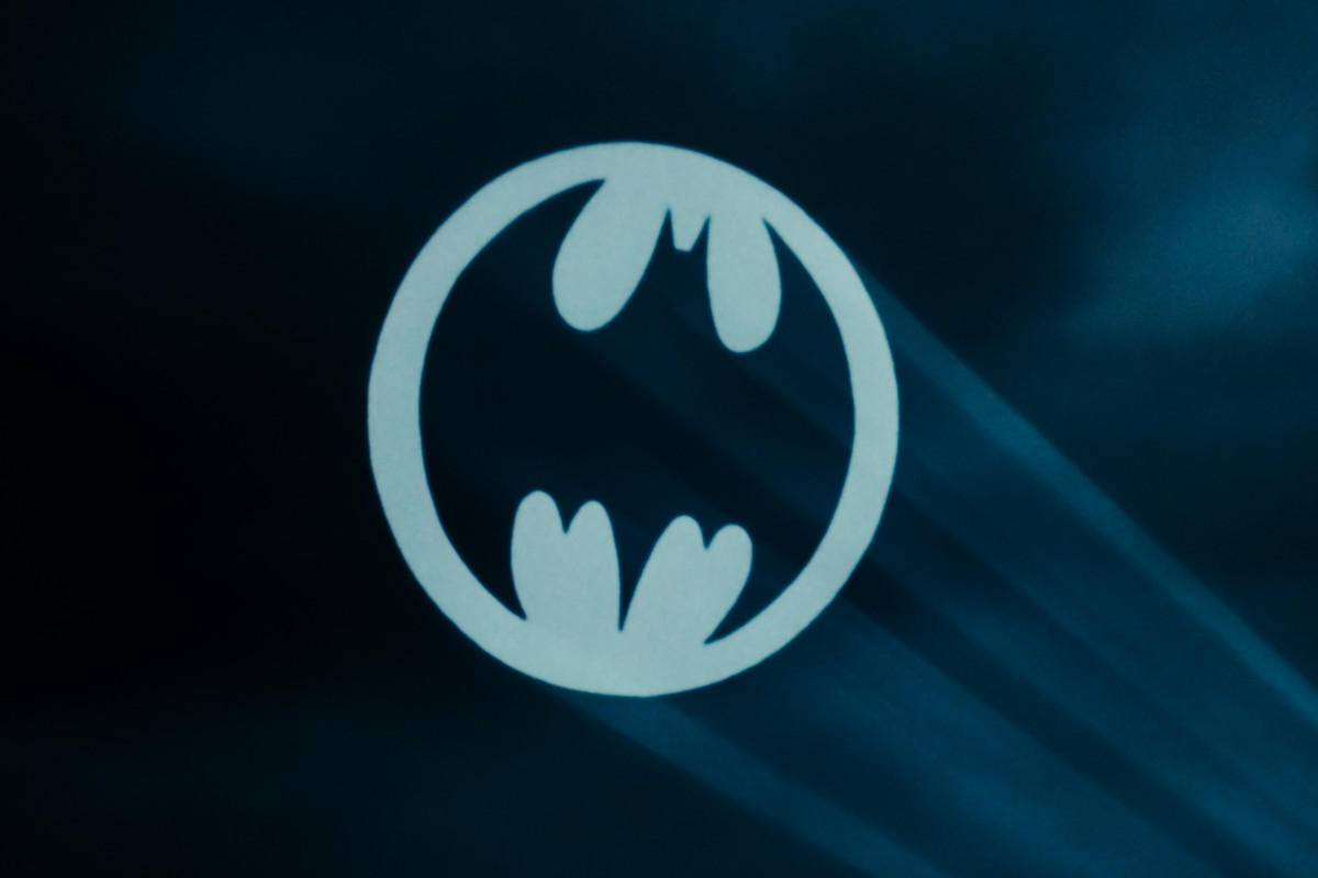the batsignal shines in a blue and black sky
