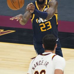 Utah Jazz's Royce O'Neale (23) passes the ball past Cleveland Cavaliers' Larry Nance Jr. (22) during the first half of an NBA basketball game Tuesday, Jan. 12, 2021, in Cleveland.