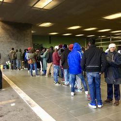 Refugees line up for food at Rome's Tiburtino train station. The food was provided by local residents.