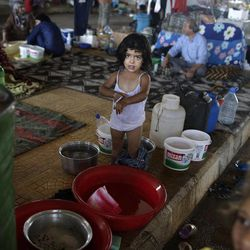 In this Friday, Sept. 7, 2012, photo, Syrian girl, Ruwa Bazara, whose family fled their home 15 days ago, due to Syrian government shelling, reacts as she waits her mother to continure giving her a bath, as she and her family take refuge at the Bab Al-Salameh border crossing, in hopes of entering one of the refugee camps in Turkey, near the Syrian town of Azaz. The days are still hot across the fertile plains of northern Syria, but at night there is a hint of a chill an ominous harbinger of winter's approach and the deepening of the humanitarian crisis gripping a country wracked by civil war.