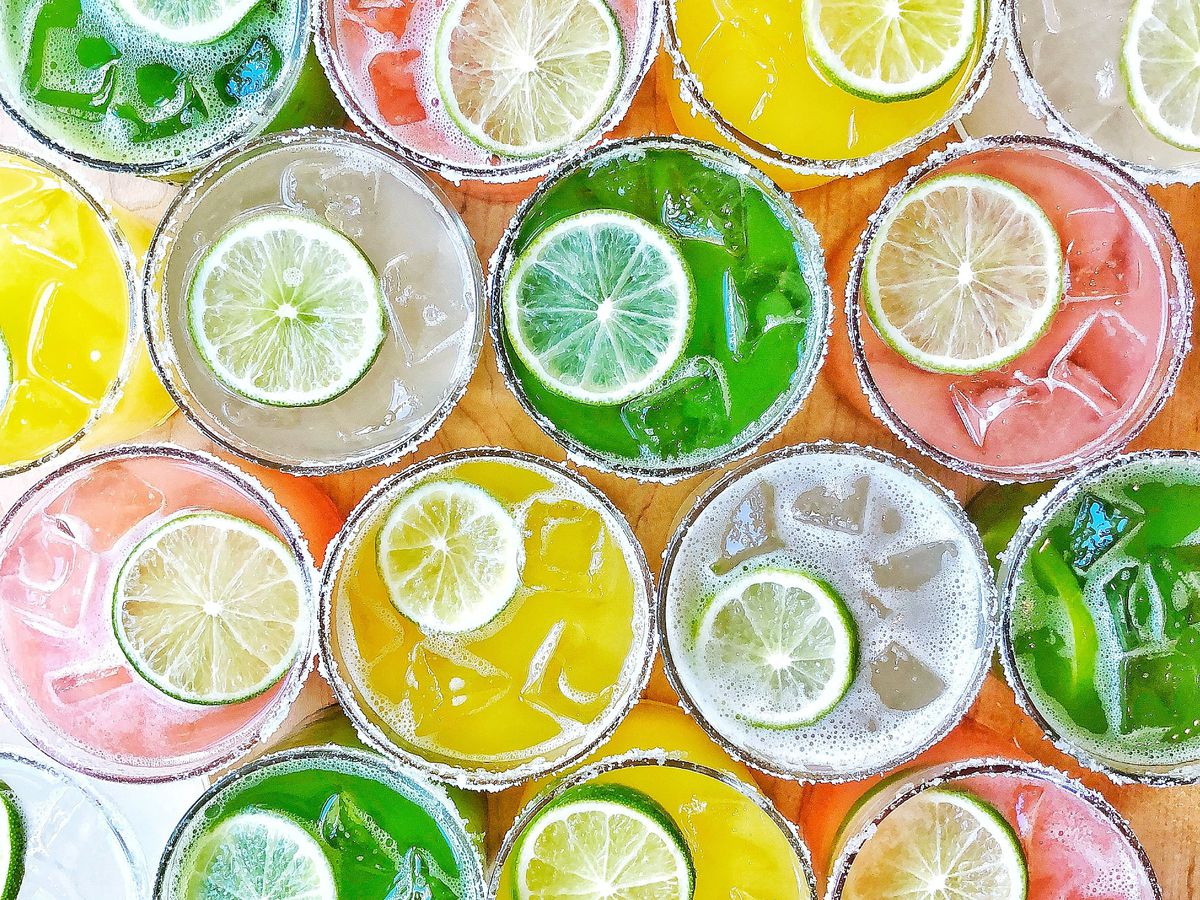 overhead shot of colorful margaritas with limes