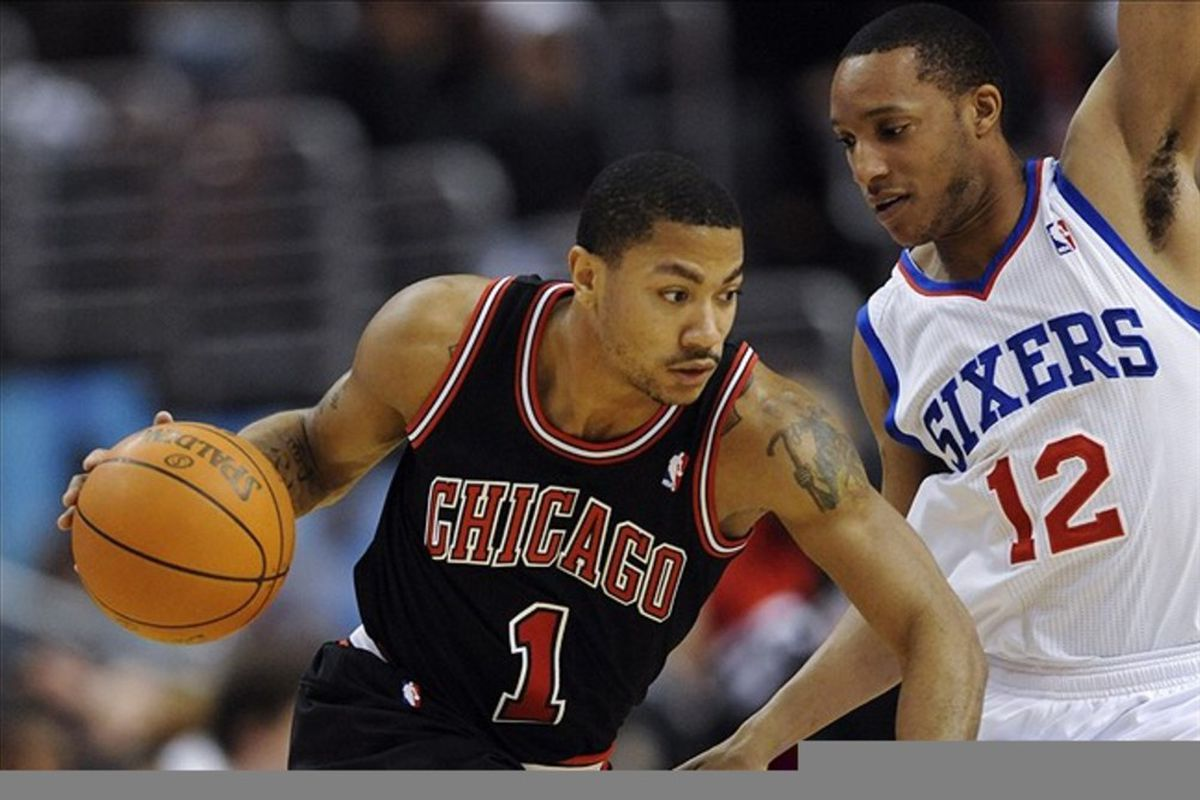 Mar 04, 2012; Philadelphia, PA, USA; Chicago Bulls guard Derrick Rose (1) is defended by Philadelphia 76ers guard Evan Turner (12) during the first quarter at the Wells Fargo Center. Mandatory Credit: Howard Smith-US PRESSWIRE