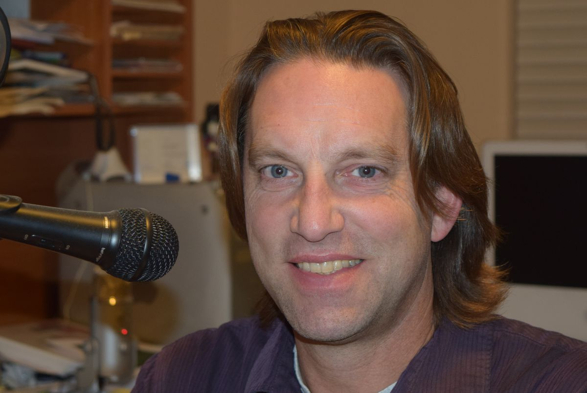 A headshot of Michael Polkinghorn with a microphone.