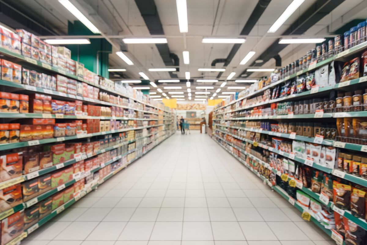Shelves filled with goods in a grocery store aisle lit by florescent lighting, blurry view.