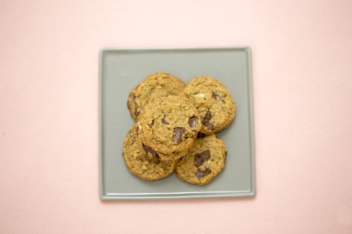 An overhead photograph of five chocolate chip cookies on a silver tray placed on top of a millennial pink countertop
