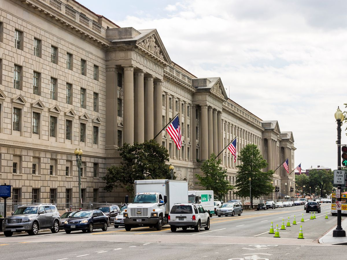 The exterior of the Herbert Hoover Building in Washington D.C.  The facade is tan with columns.