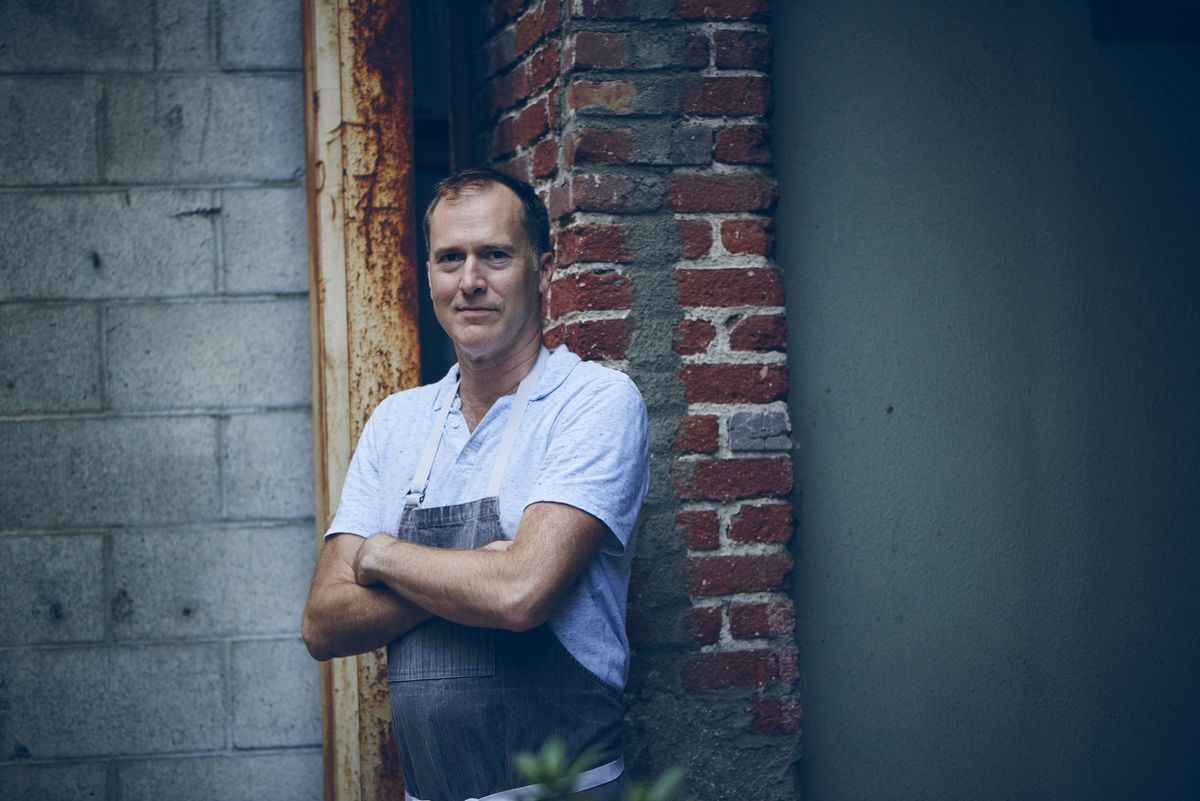 Lincoln Carson, a chef, stands arms crossed at a window looking into his restaurant space.