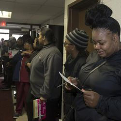Da'Lenn Kirby, 38, far right, fills out her application to vote at Bethel AME Church in Detroit, Mich., on Nov. 8, 2016.