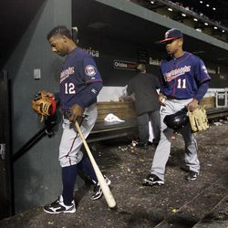 Minnesota Twins' Alexi Casilla (12) and Ben Revere walk out of the dugout after a baseball game against the Baltimore Orioles in Baltimore, Saturday, April 7, 2012. Baltimore won 8-2.