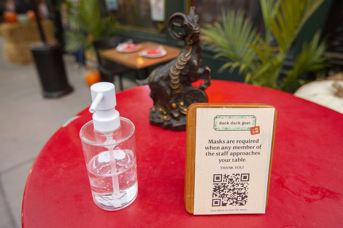 A red table with hand sanitizer and QR code, plus a goat statue.