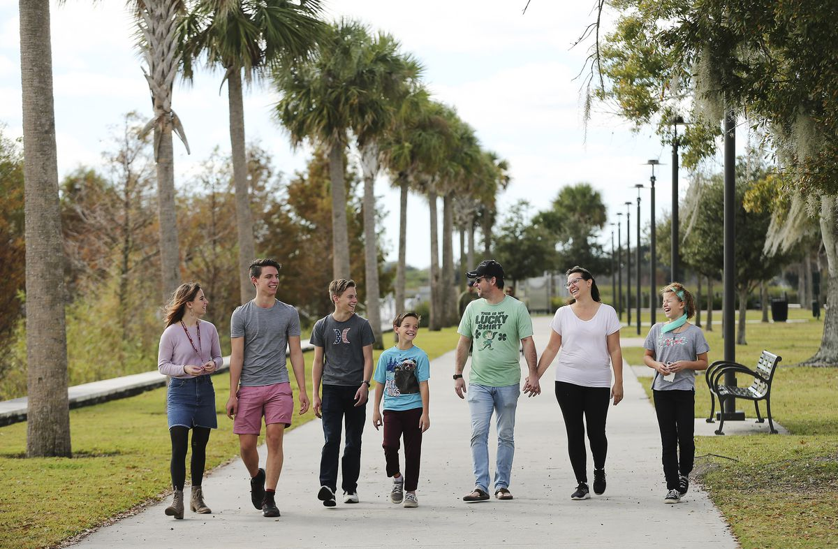 Tom and Heather Wakefield, fourth and fifth from left, walk at Kissimmee Lakefront Park with their children — Kelsie, left, Taylor, Adam, Lincoln and Xande — in Kissimmee, Fla., on Monday Dec. 21, 2020.