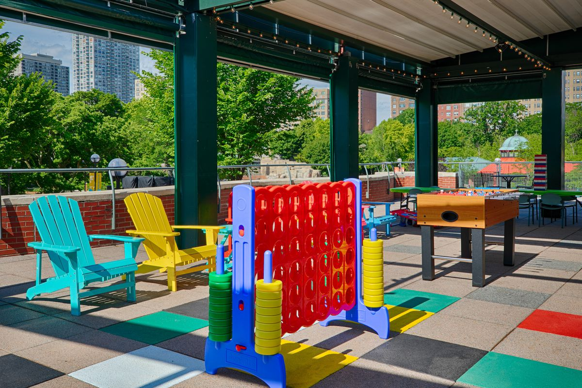 two Adirondack chairs, a giant Connect Four set, and a Foosball table