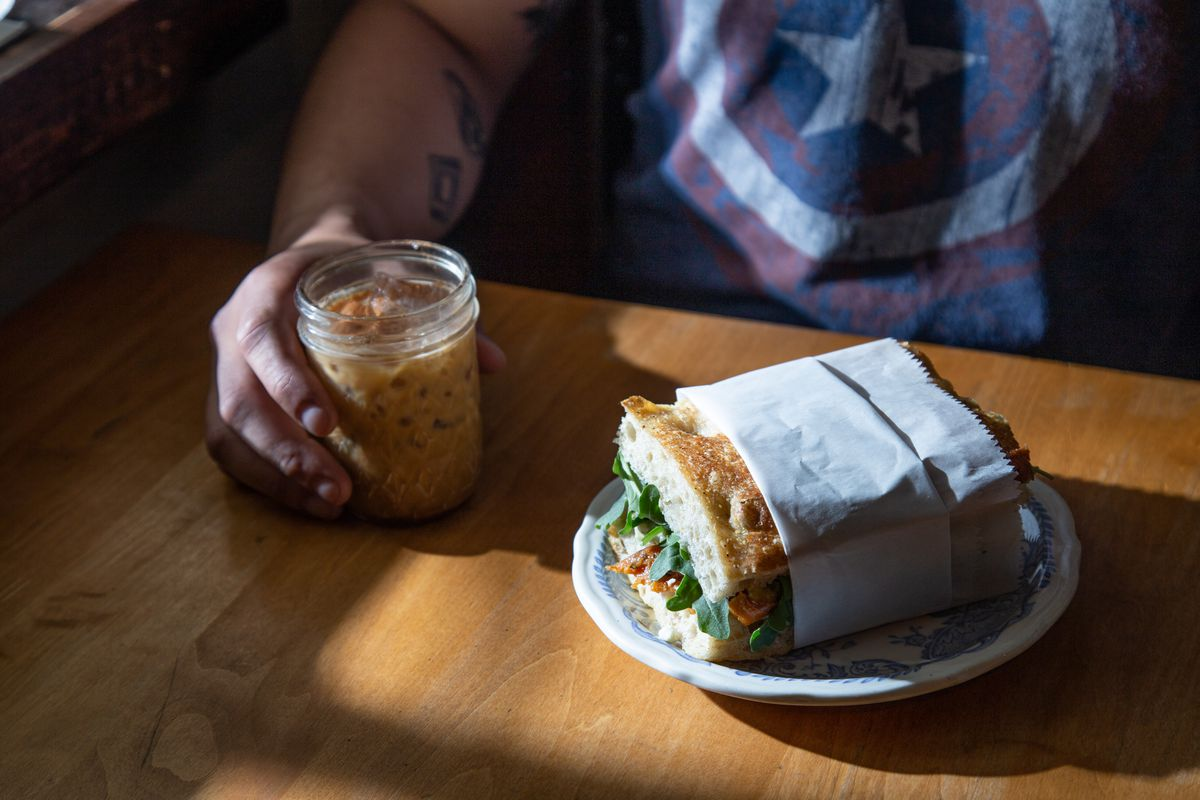a hand cradling an iced coffee in a mason jar and a focaccia sandwich wrapped in paper on a plate