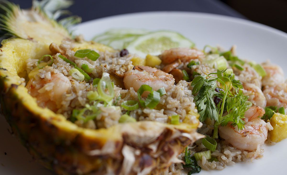 A hollowed out pineapple overflows with shrimp, rice, and herbs on a large plate