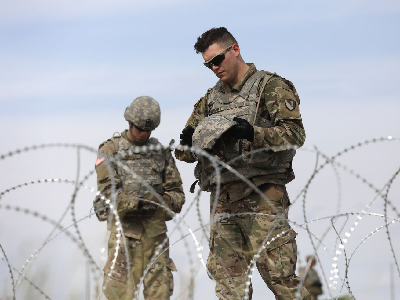 US Army soldiers pause from the heat while stringing razor wire near the port of entry at the US-Mexico border on November 4, 2018, in Donna, Texas.