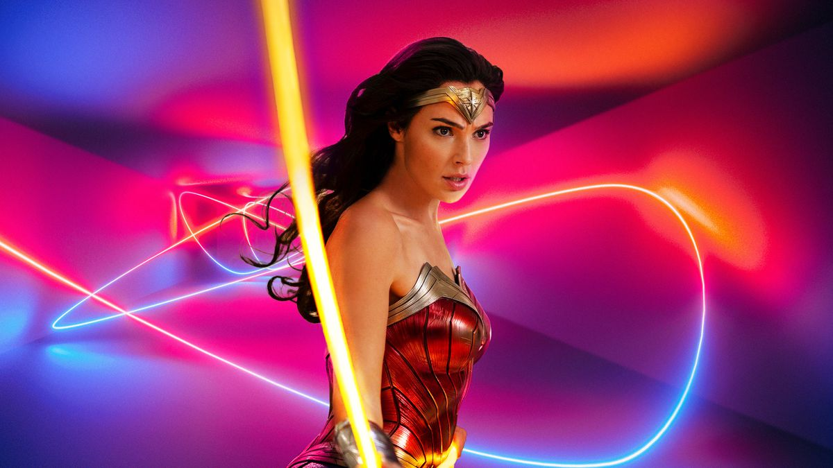 Gal Gadot as Diana flipping her lasso of truth in Wonder Woman 1984, on a blue, red, and purple background