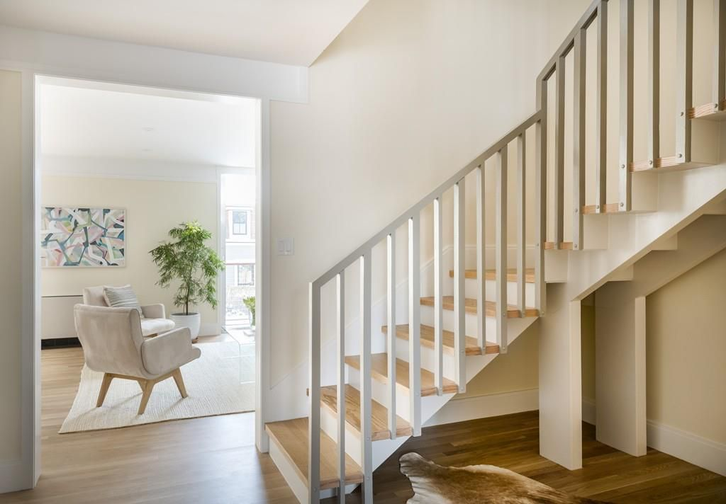 An entry foyer with a sparse and stylish staircase, and there's a living room visible through door-less door.