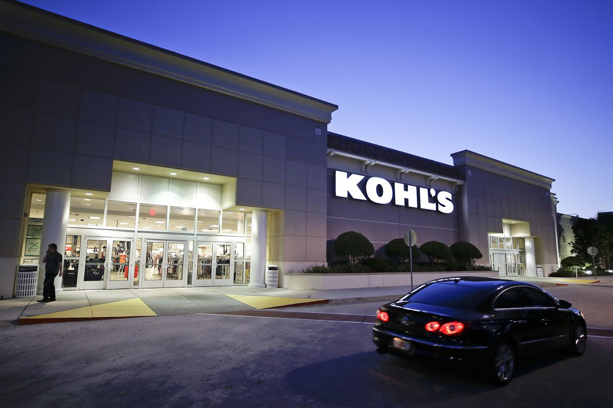 FILE - In this Aug. 22, 2017, file photo, a car drives by the entrance of a Kohl's department store in Orlando, Fla. Kohl's wants you to skip the post office and bring your Amazon returns to its stores.