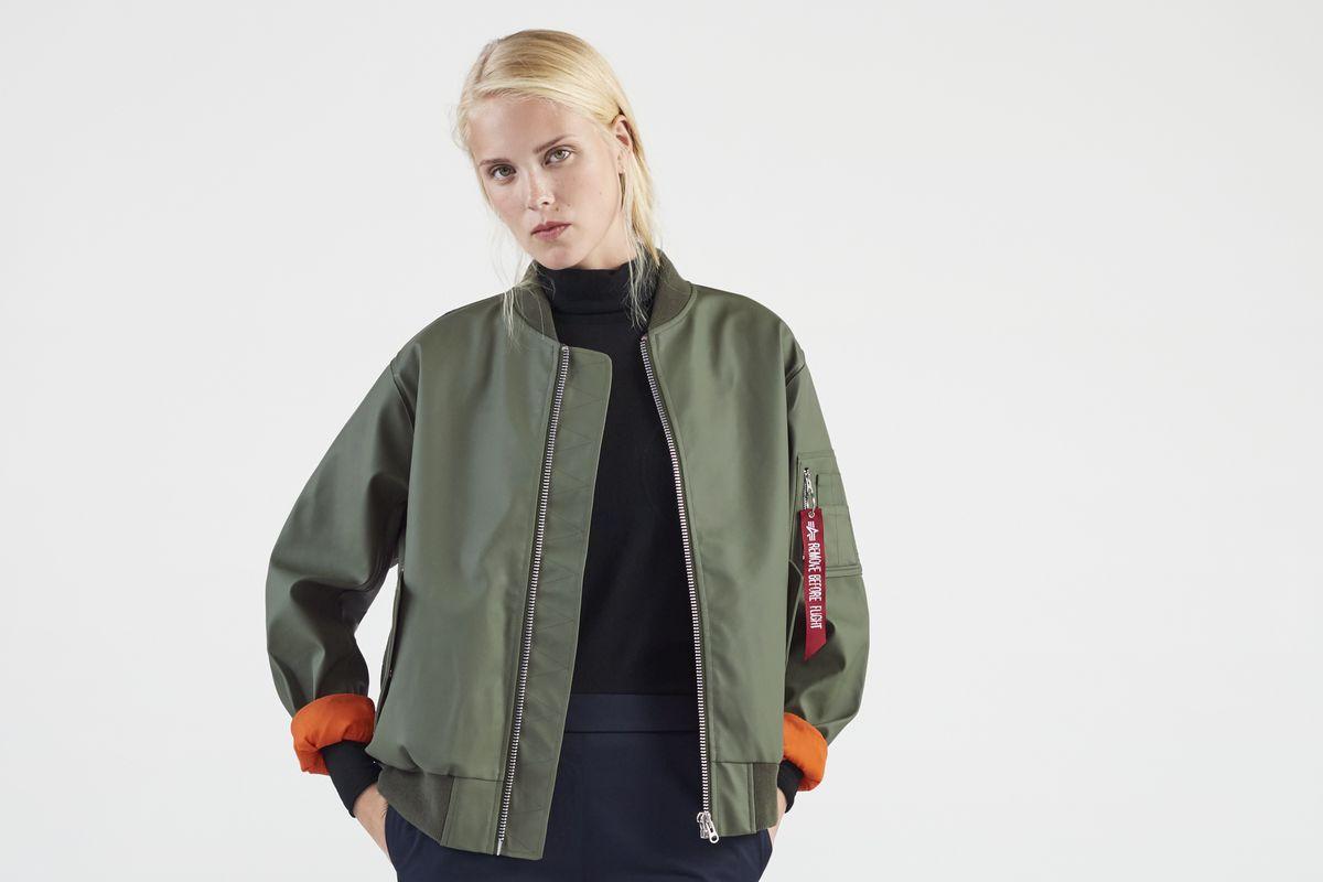 A model in a green waterproof bomber jacket.