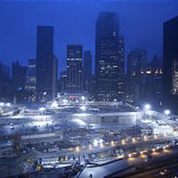 The patch of land that once held the World Trade Center is bathed in the glow from dozens of stadium lights.