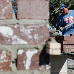 A hod tender shovels concrete during the Spec Mix Bricklayer 500 regional competition at Interstate Brick in West Jordan on Friday, Oct. 9, 2020.