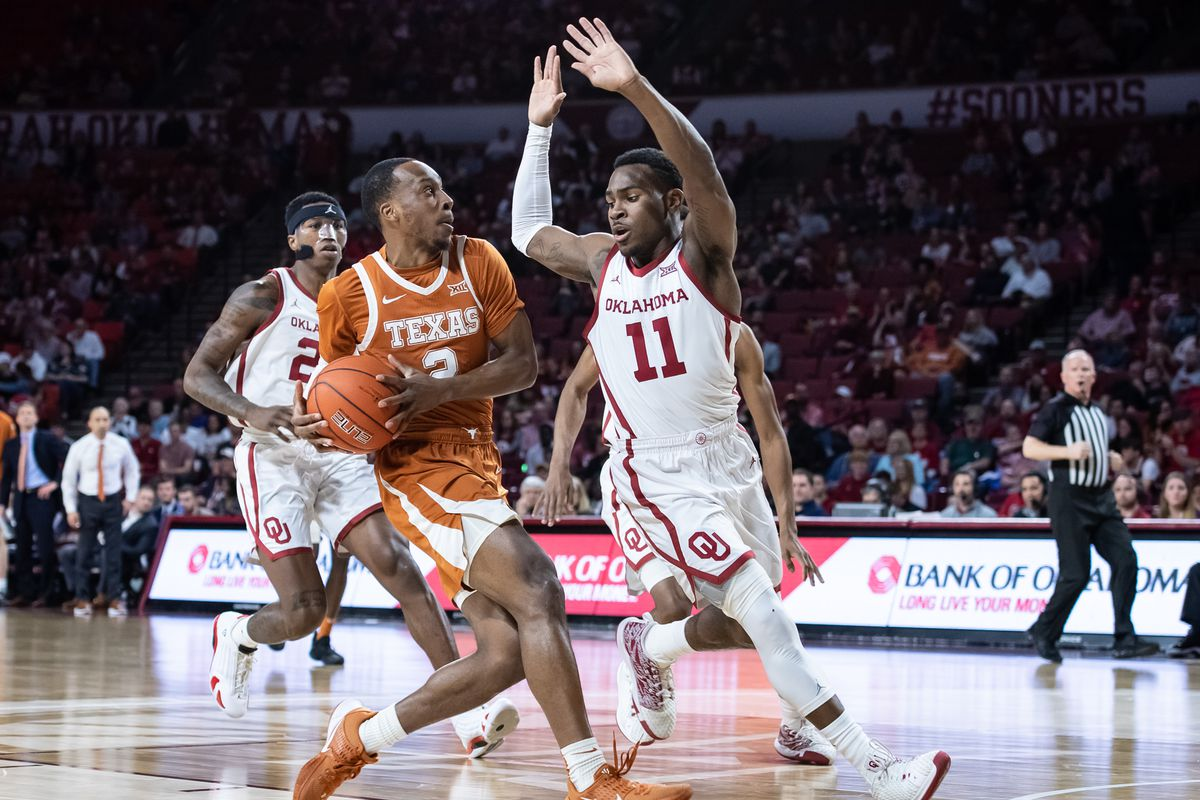 Texas Longhorns guard Matt Coleman III drives to the basket defended by Oklahoma Sooners guard De'Vion Harmon during the first half at Lloyd Noble Center.