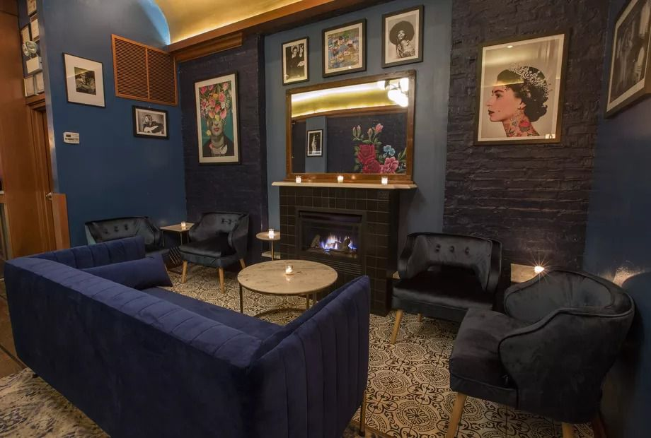 The lounge features framed artwork, blue seats, and a fireplace.