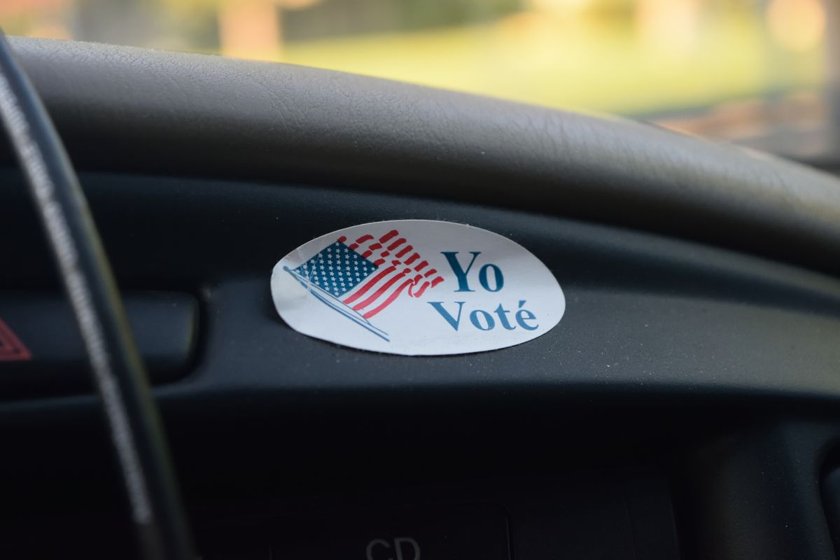 """A photo of part of a matte black car fender with a white oval sticker that reads """"Yo Voté"""" (""""I voted"""")  in blue letters and has an image of American flag on it."""