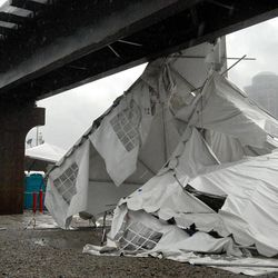 A party tent from Kilroy's Sports Bar in St. Louis rests against a railroad trestle near the bar after storm winds blew through the area following a baseball game between the St. Louis Cardinals and Milwaukee Brewers at nearby Busch Stadium Saturday, April 28, 2012. One person died Saturday and more than a dozen were taken to a hospital with injuries after high winds blew over a beer tent near Busch Stadium in St. Louis.