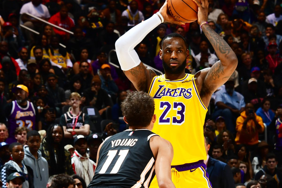 LeBron James #23 of the Los Angeles Lakers handles the ball against Trae Young #11 of the Atlanta Hawks on December 15, 2019 at State Farm Arena in Atlanta, Georgia.