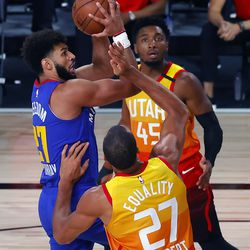 Denver Nuggets' Jamal Murray drives against Utah Jazz' Rudy Gobert (27) as Jazz teammate Donovan Mitchell (45) looks on during an NBA basketball game Saturday, Aug. 8, 2020, in Lake Buena Vista, Fla.