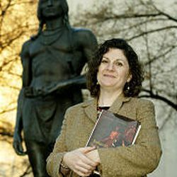 BYU's Jenny Hale Pulsipher holds her book near an Indian statue on campus. The book offers revealing information on Pilgrims and Indians.
