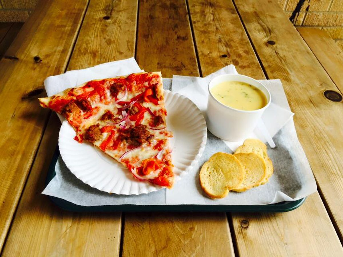 A slice of pizza with meat, tomatoes, and onions on a paper plate next to a cup of broccoli/cheese/rice soup and slces of bread, all on a tray on a wooden table