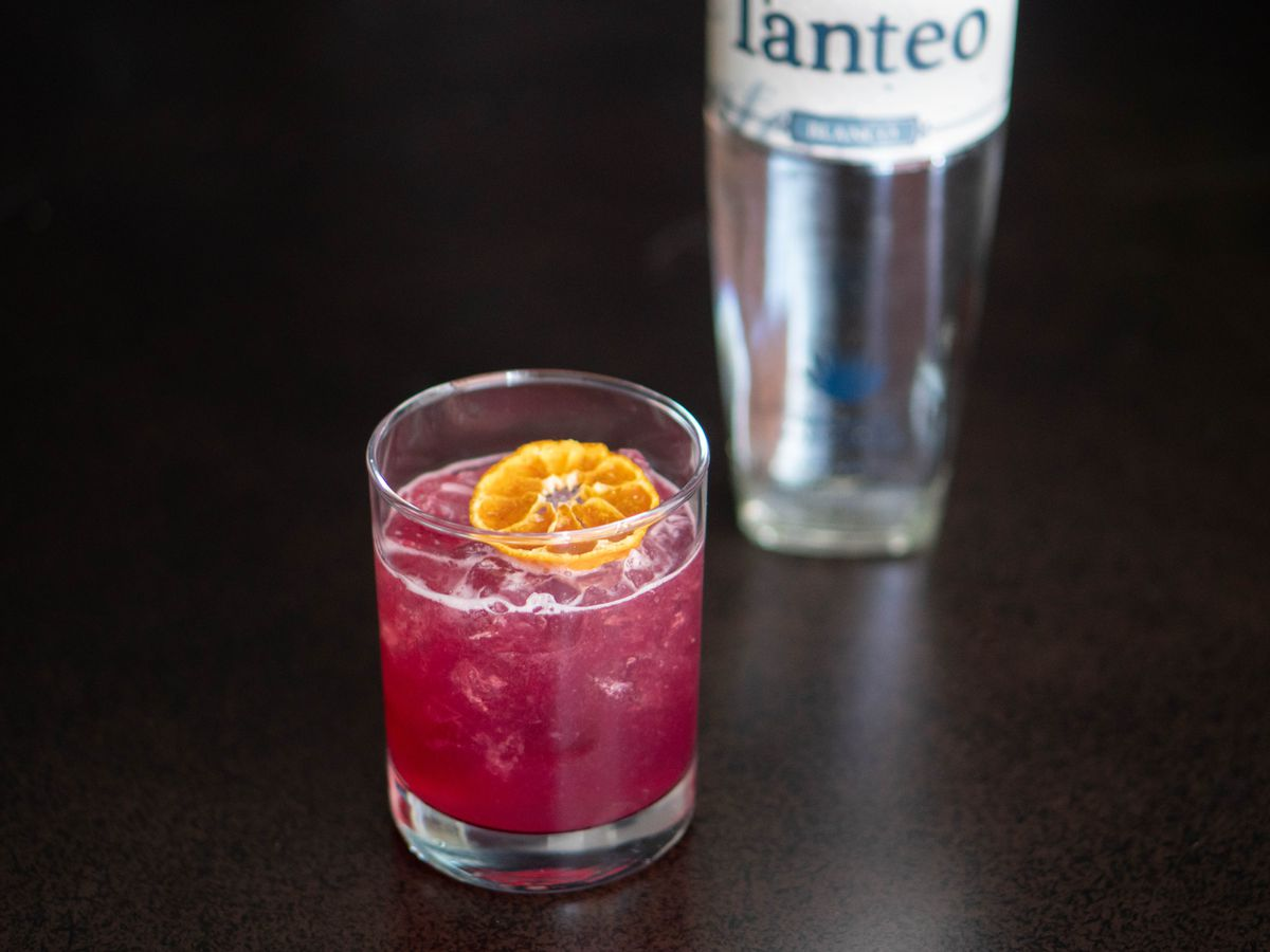A small purple-ish cocktail on ice with an orange slice floating in it