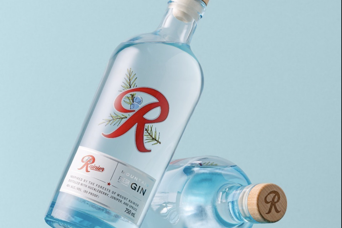 Two clear bottles of Rainier Mountain Fresh Gin against a light blue background