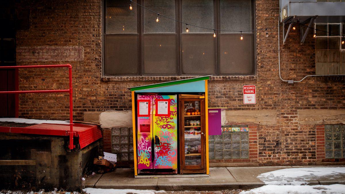 A brightly painted community refrigerator sitting on a city sidewalk.