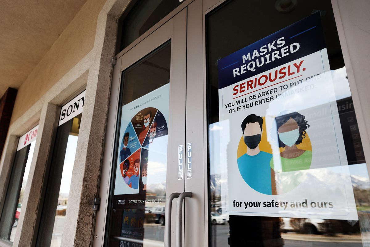 """""""Masks required"""" signage is pictured on the front doors of Pixels Foto & Frame in Sandy on Monday, April 5, 2021."""