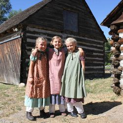 Bella Evans, Stella Shurtz and Margaret Moffett, descendants of John Rowe Moyle, pose in front of an old pioneer cabin at Moyle Park in July 2014. The three cousins get to see each other every week for the park's pioneer activities.