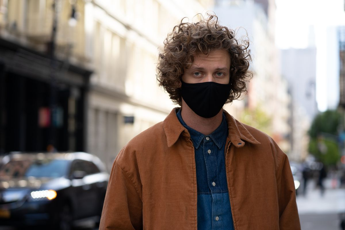 Man standing on an urban street wears a black face mask, orange corduroy jacket paired with a multi colored blue chambray denim shirt.