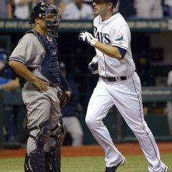 Tampa Bay Rays' Matt Joyce, right, runs past New York Yankees catcher Russell Martin after hitting a solo home run during the third inning of a baseball game in St. Petersburg, Fla., Saturday, April 7, 2012.